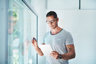 Buy stock photo Shot of a mature businessman using a digital tablet while writing notes on a glass wall in an office