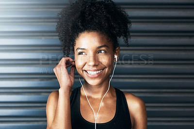 Buy stock photo Shot of a sporty young woman listening to music while exercising against a grey background