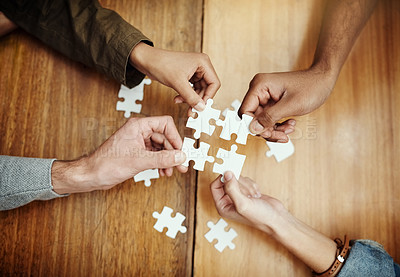 Buy stock photo High angle shot of a group of unrecognizable university students building a puzzle while studying in the library