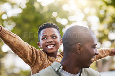 Buy stock photo Shot of a father giving his son a piggyback ride outdoors