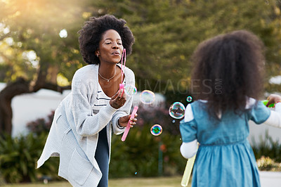 Buy stock photo Shot of a mother and her little daughter playing with bubbles together outdoors
