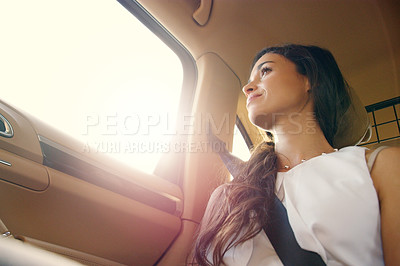 Buy stock photo Shot of an attractive young businesswoman sitting inside a car and looking out the window while travelling to work