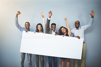 Buy stock photo Studio shot of a group of businesspeople holding a sign and cheering against a gray background