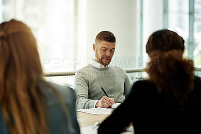 Buy stock photo Cropped shot of three businesspeople sitting around a table in the boardroom during a meeting