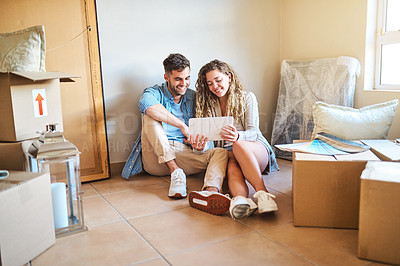 Buy stock photo Shot of a young couple using a digital tablet while moving into their new home