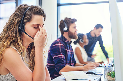 Buy stock photo Shot of a young woman experiencing stress in a call centre