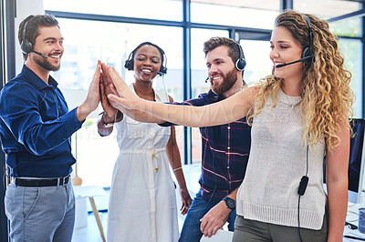 Buy stock photo Shot of a team of young people giving each other a high five while working in a call centre