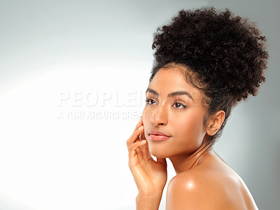 Buy stock photo Studio shot of a beautiful young woman looking thoughtful against a gray background