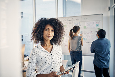 Buy stock photo Cropped portrait of an attractive young creative businesswoman working on a tablet in her office with colleagues in the background