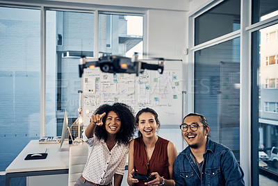Buy stock photo Cropped shot of three young creative businesspeople flying a drone in their office