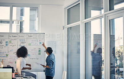 Buy stock photo Cropped shot of two young creative businesspeople working on a whiteboard during a meeting in their office at night