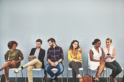 Buy stock photo Shot of a group of businesspeople using their wireless devices while sitting in a row