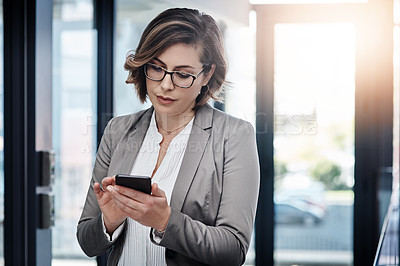 Buy stock photo Shot of a young businesswoman using a smartphone in a modern office