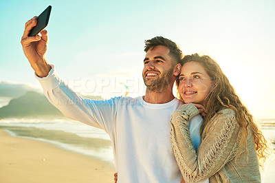 Buy stock photo Cropped shot of an affectionate young couple taking selfies at the beach