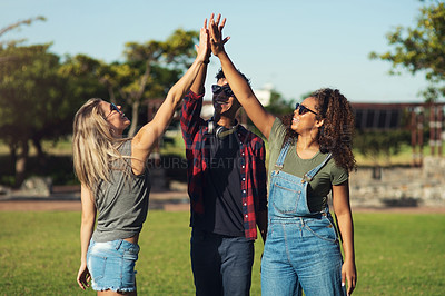 Buy stock photo Shot of a group of cheerful young friends giving each other high fives outside in a park