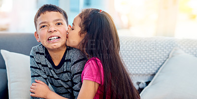 Buy stock photo Shot of an adorable little girl kissing her big brother on the cheek at home