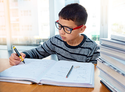 Buy stock photo Shot of a determined young boy doing his homework at home