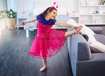Buy stock photo Shot of an adorable little girl dressed up as a fairy showing off her ballet moves at home