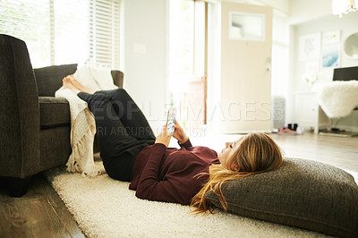 Buy stock photo Shot of a young woman using a smartphone while relaxing at home