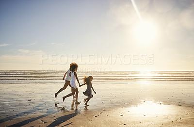 Buy stock photo Shot of a happy family running along the beach