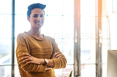 Buy stock photo Cropped portrait of a confident and attractive young businesswoman standing with her arms crossed in an office