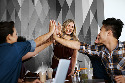 Buy stock photo Cropped shot of a group of designers high fiving during a meeting in their creative office