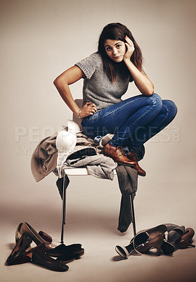 Buy stock photo Studio shot of a young woman trying to choose an outfit from a pile of clothes against a brown background