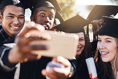 Buy stock photo Shot of a group of students taking selfies with a mobile phone on graduation day