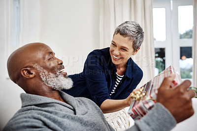 Buy stock photo Shot of an attractive senior woman surprising her husband with a gift at home