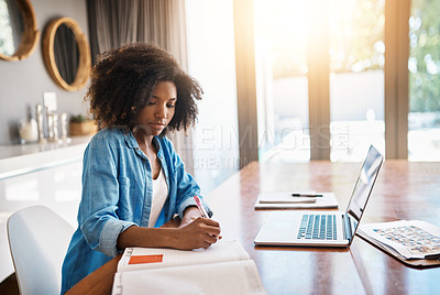 Buy stock photo Shot of an attracting young woman writing notes on a book at home