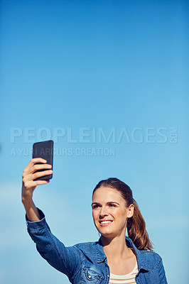 Buy stock photo Shot of an attractive young woman taking a selfie outdoors