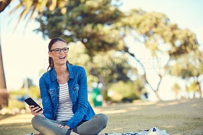 Buy stock photo Shot of an attractive young woman using a mobile phone while relaxing in the park