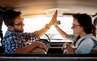 Buy stock photo Rearview portrait of an affectionate couple giving each other a high five while enjoying a road trip
