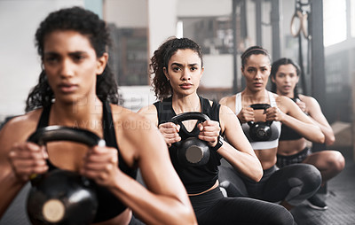 Buy stock photo Shot of a group of fit young women working out with kettle bells at the gym