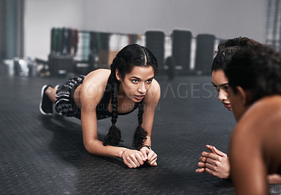 Buy stock photo Shot of fit young women doing plank exercises together at the gym