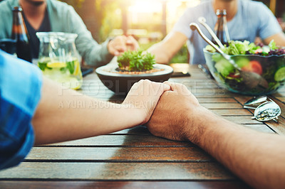 Buy stock photo Closeup shot of an unrecognizable group of young friends holding hands together around a table outside in a garden