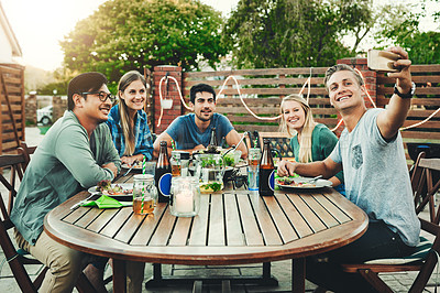 Buy stock photo Shot of a group of young friends posing together around a table while taking a selfie outdoors