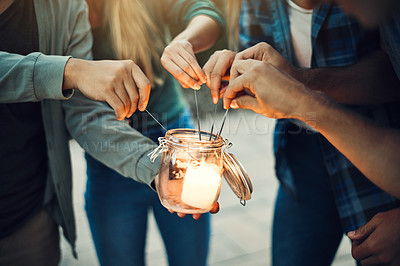 Buy stock photo Shot of a group unrecognizable people's hands lighting up sparklers together outside