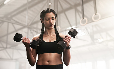 Buy stock photo Shot of a sporty young woman lifting weights in a gym