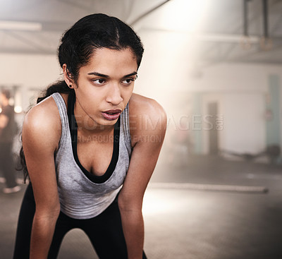 Buy stock photo Shot of a sporty young woman taking a break while working out at the gym