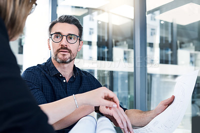 Buy stock photo Shot of two businesspeople analyzing blueprints in an office