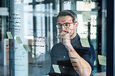 Buy stock photo Shot of a mature businessman brainstorming notes on a glass wall in an office