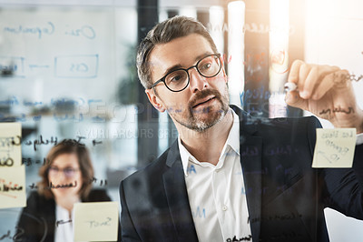 Buy stock photo Shot of a mature businessman presenting notes on a glass wall to his colleague in an office
