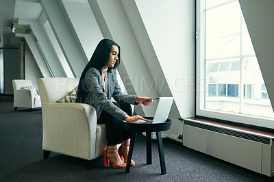 Buy stock photo Full length shot of an attractive young businesswoman working on her laptop in the office