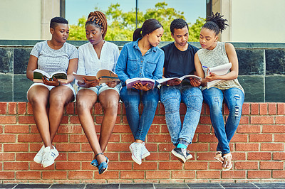 Buy stock photo Full length shot of a group of young university students sitting with their books on a wall on campus