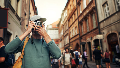 Buy stock photo Cropped shot of a young man taking photos while exploring a foreign city