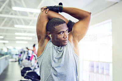 Buy stock photo Cropped shot of a handsome young athletic man warming up in the gym