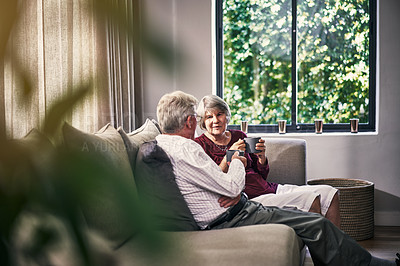Buy stock photo Cropped shot of an affectionate senior couple enjoying a cup of coffee in their retirement home