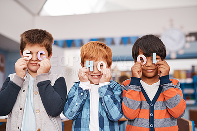 Buy stock photo Cropped shot of a group of cheerful elementary school children holding letters over their faces spelling the word school inside of the classroom