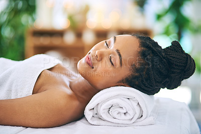 Buy stock photo Shot of an attractive young woman relaxing on a massage table at a spa